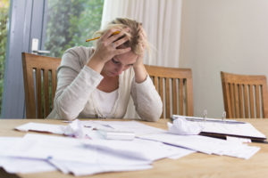 unexpected income loss woman stressed about paying bills