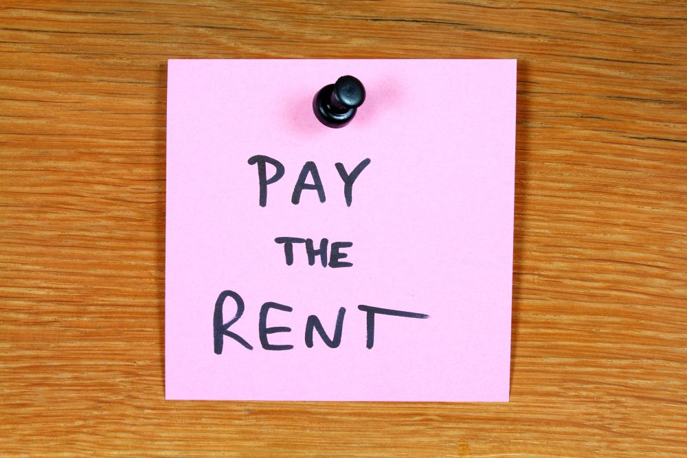 pay the rent post-it note on wood door