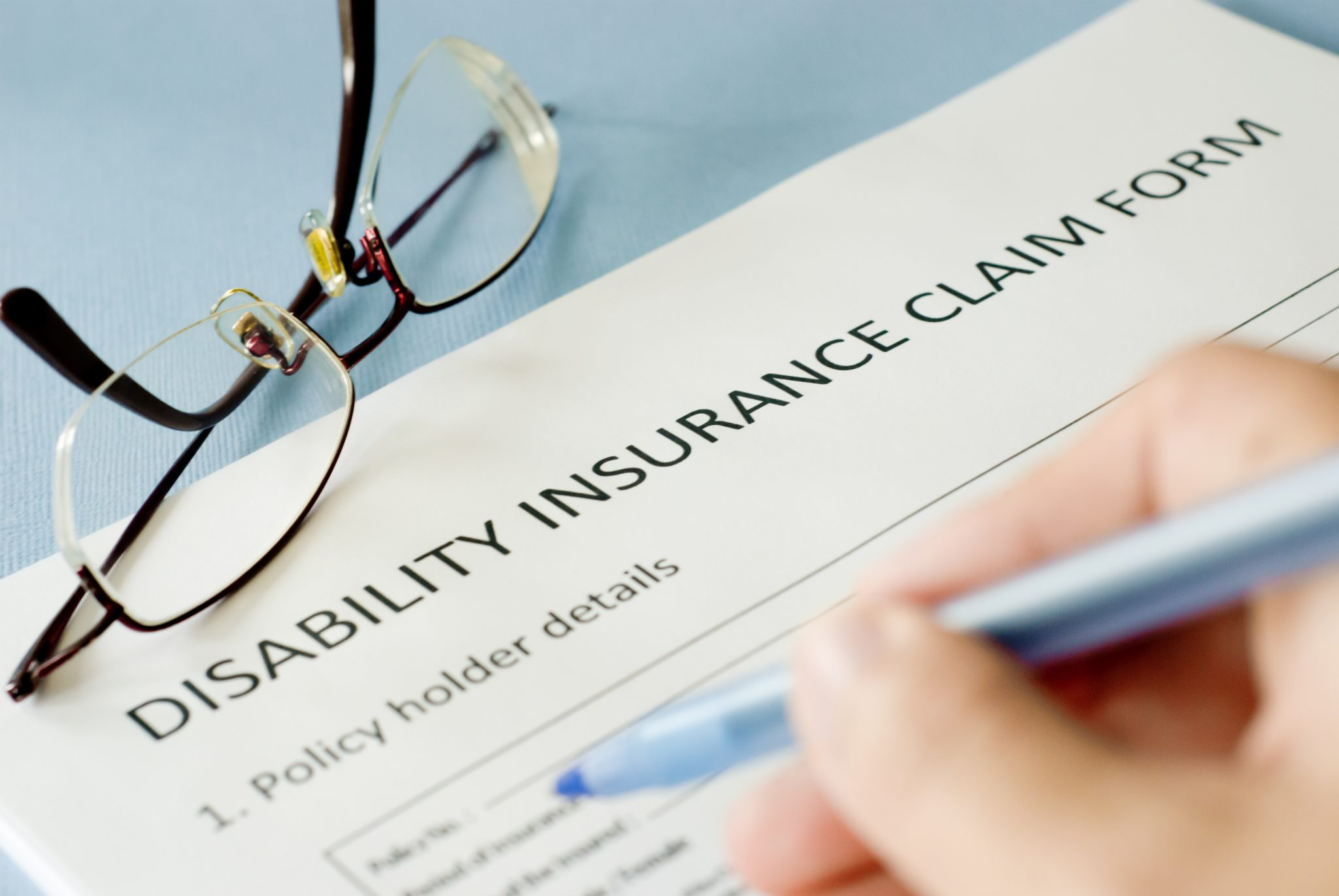 signing insurance claim form on blue background