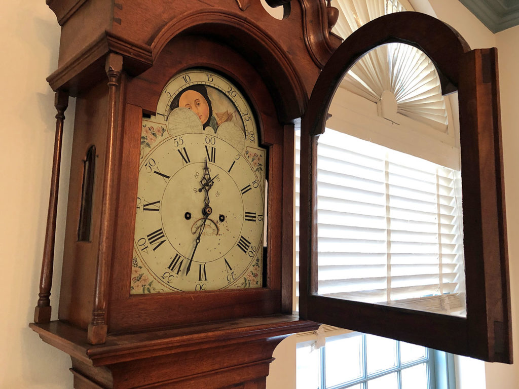 antique grandfather clock with door open to expose dials