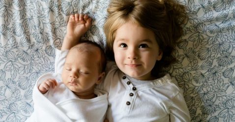 ddler and newborn brothers laying on a bed sleeping and smiling